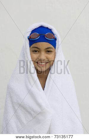 Hispanic girl in towel with swimming cap and goggles