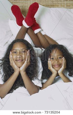 Two African American sisters on bed