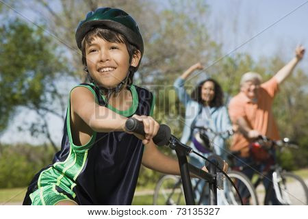 Hispanic boy on bicycle with family in background