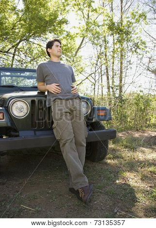 Young man leaning on jeep in woods