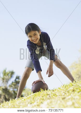 Young Hispanic girl hiking football