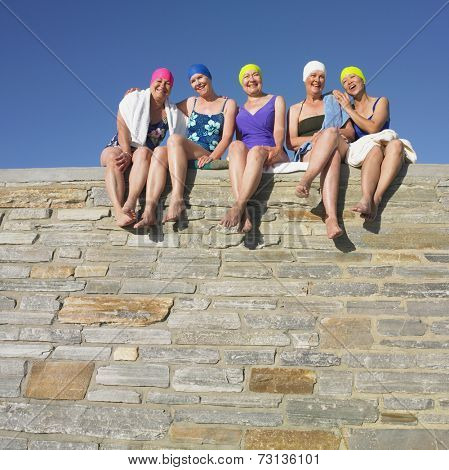Group of senior women in bathing suits sitting on stone wall