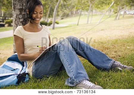 Young African woman with backpack leaning on tree and writing
