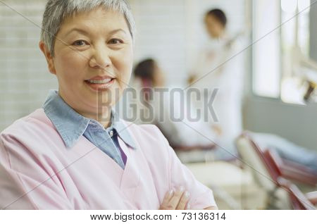 Senior Asian female dental assistant with dentist and patient in background
