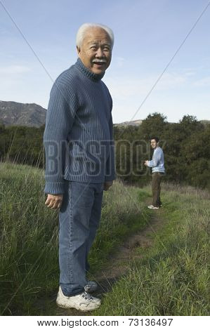 Senior man smiling on dirt path