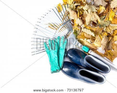 Pile of dead fall leaves, fan rake, pair of gumboots, and pair of gardening gloves all shot on white