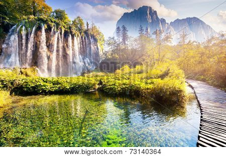 Majestic view on waterfall with turquoise water and sunny beams in the Plitvice Lakes National Park. Forest glowing by sunlight. Croatia. Europe. Dramatic morning scene. Beauty world.