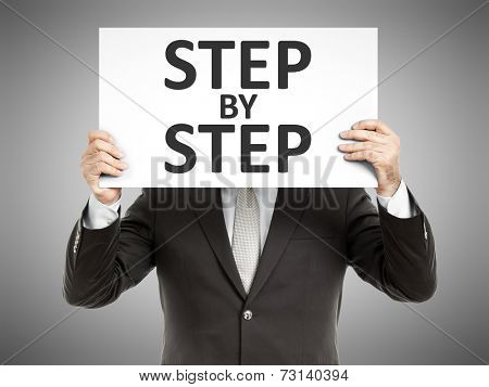 A business man holding a paper in front of his face with the text step by step