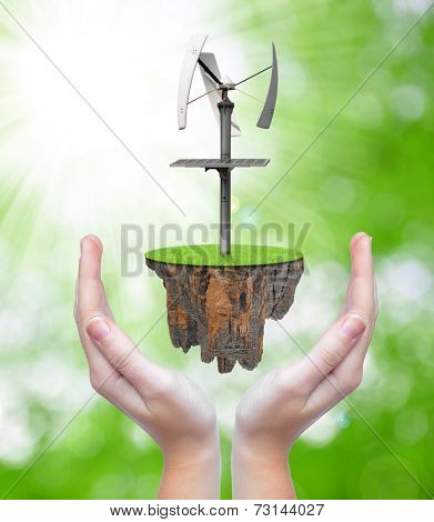 Little island with wind turbine in hands