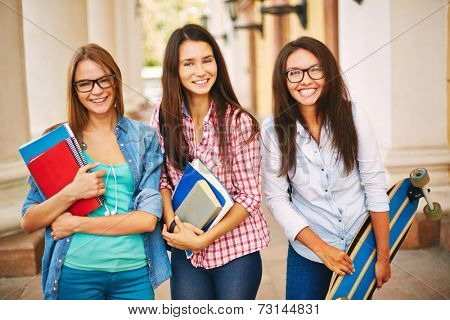 Team of ecstatic girls looking at camera white standing by their college