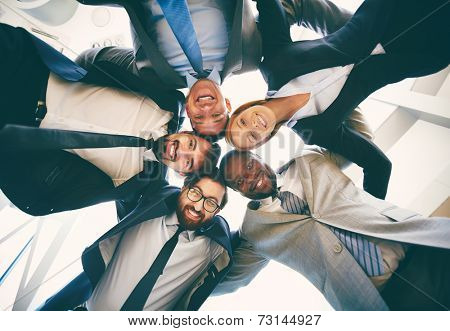 Group of friendly businesspeople in suits looking at camera while standing head to head, below view