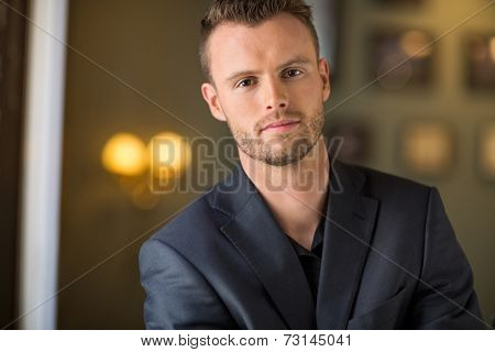 Portrait of confident young businessman at coffeeshop