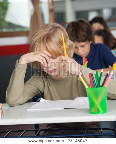 Bored schoolboy with hand on face sitting at desk in classroom