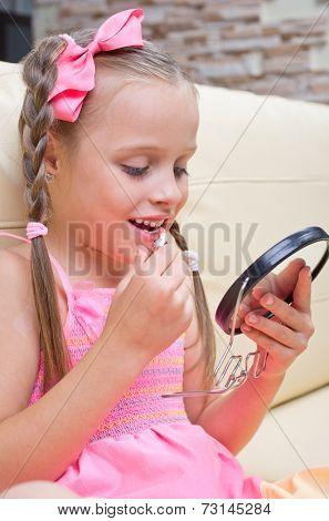 Little girl puts makeup in light room