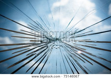 Broken Glass with Blue Sky and Clouds in Background.