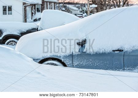 A truck and a car in a driveway in a suburban neighborhood buried in new fallen snow.