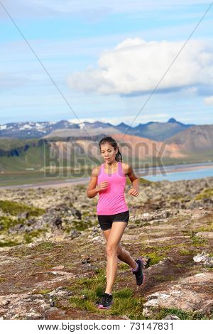 Athlete runner woman running in nature. Female fitness girl cross country trail running in amazing nature landscape outside. Image from Iceland.