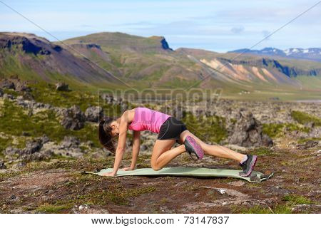 Exercising fitness woman doing exercises in nature. Girl doing mountain climbers exercise training outside in amazing landscape on Iceland. Fit female Asian Caucasian athlete sport model .