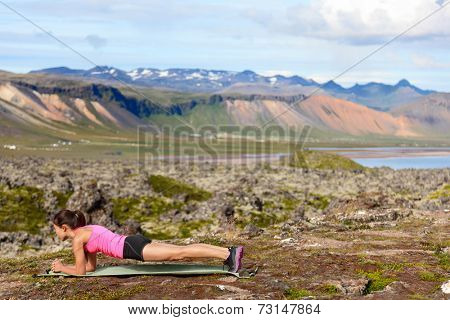 Exercising fitness woman doing plank in nature training core outside in amazing nature landscape on Iceland. Fit female sport model girl training outdoors. Mixed race Asian Caucasian athlete.