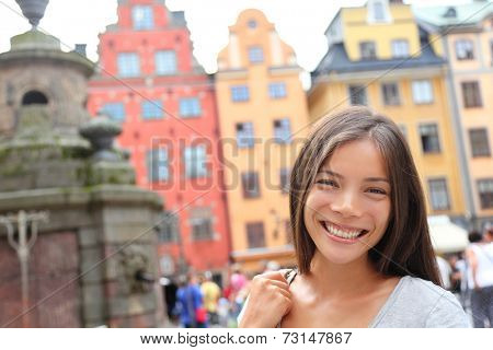 Woman portrait in Europe, Stortorget, Stockholm, Sweden. Happy candid travel tourist girl on big square in Gamla Stan, the old town of Stockholm, Sweden.