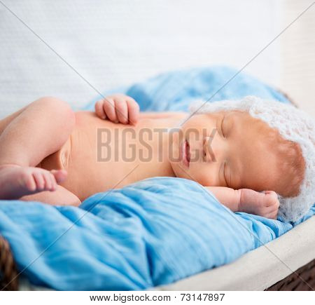 newborn boy sleeping in a basket on a blue bedspread