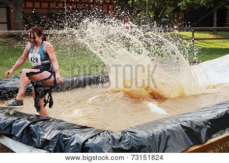 MUSKOGEE, OK - Sept. 13: An athlete slides into a muddy pit to avoid zombies during the Castle Zombie Run at the Castle of Muskogee in Muskogee, OK on September 13, 2014.
