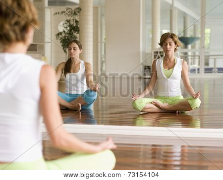 Two Hispanic women meditating at health club