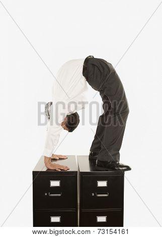 Businessman doing a back bend on filing cabinet