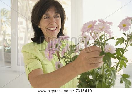 Senior woman arranging flowers in vase