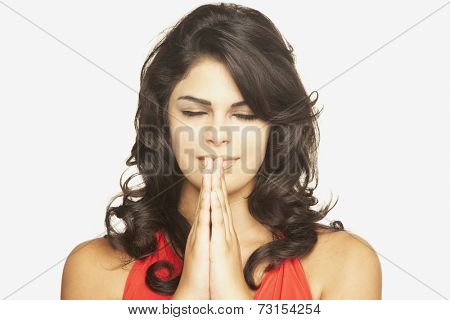 Hispanic woman praying with eyes closed