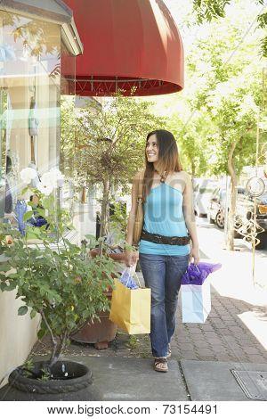Hispanic woman on sidewalk holding shopping bags