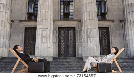 Businesspeople in lounge chairs in front of building