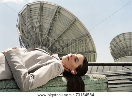 Hispanic businesswoman wearing earbuds next to satellite dishes