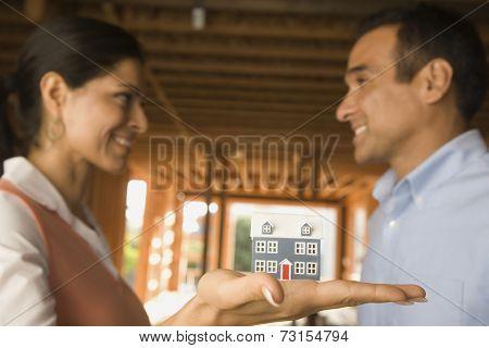 Hispanic couple holding model house at construction site