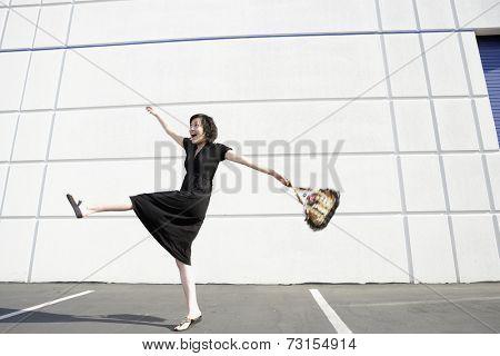 Asian woman kicking up leg in parking lot
