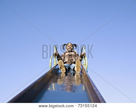 Low angle view of African girl at top of slide