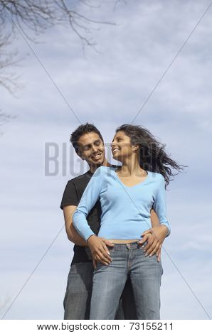 Low angle view of couple hugging