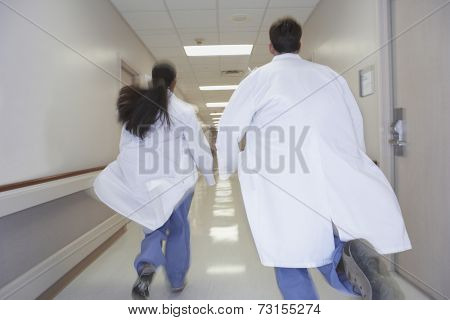 Rear view of doctors running down corridor in hospital