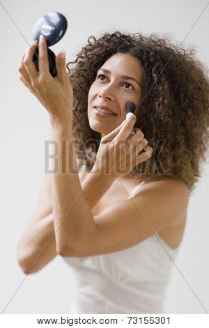 Studio shot of Hispanic woman applying makeup