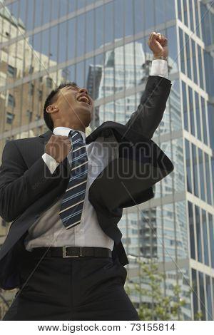 Asian businessman cheering in front of sky scraper