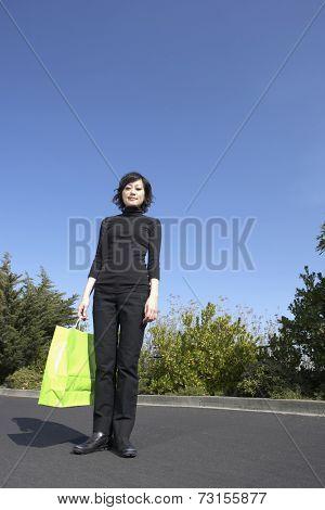 Asian woman holding shopping bag outdoors