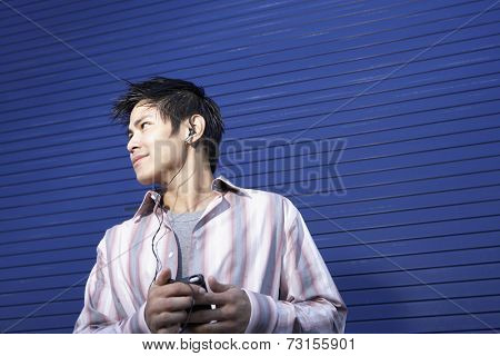 Pacific Islander man listening to mp3 player
