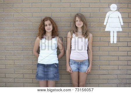 Two teenage girls leaning against wall next to restroom sign