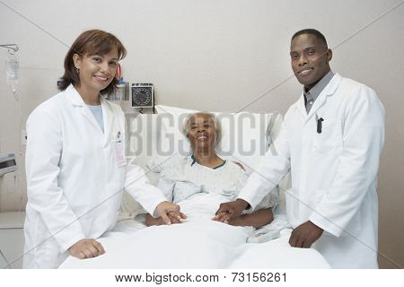 African female and male doctors holding hands with senior patient in hospital bed