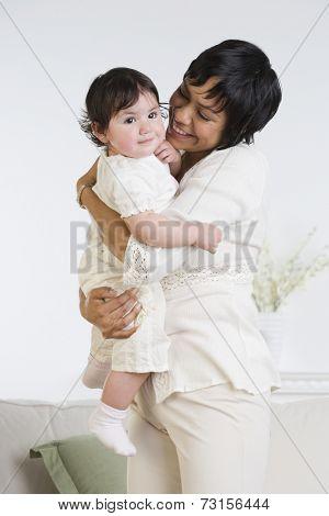 Hispanic mother smiling at baby