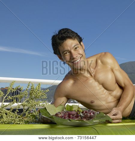 Bare-chested Asian man laying on banana leaves with fruit platter