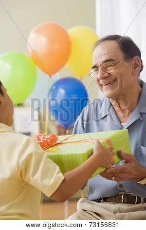 Hispanic grandfather and grandson exchanging birthday gifts
