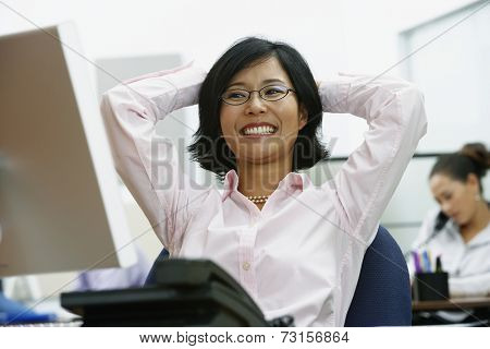 Portrait of Asian businesswoman with arms behind head