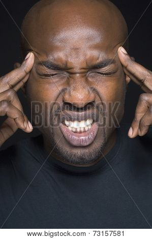 Close up of African man rubbing temples