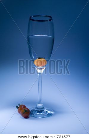 Tomato Inside The Glass In Light Blue Background